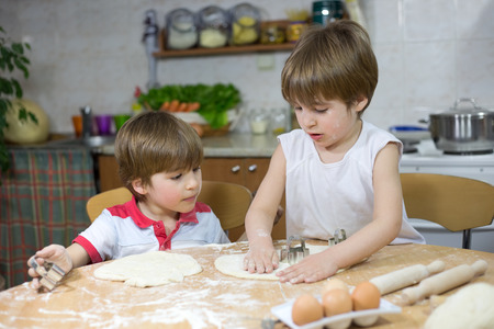 flatten: Cute Little Boy Showing His Twin Brother How to Flatten Dough at the Kitchen Table at Home Stock Photo