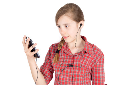 portable mp3 player: Side View of Smiling Young Girl With Earbuds  Listening to Music on Her Cellphone Isolated on White Background HalfLength Studio Shot