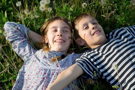 niños riendose: Niños que mienten en la hierba con los brazos extendidos y Disfrutar Sunny Spring Day View From the Top Sonreír