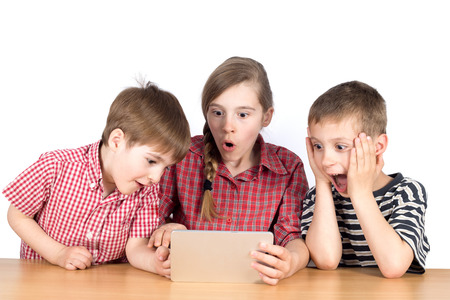 frienship: Group of Children Playing Exciting Game on Tablet HalfLength Studio Shot Isolated on White