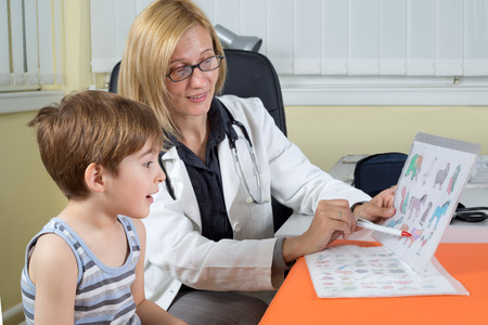 animal health: Female Doctor Examining a Three Year Old Boy in Consulting Room Stock Photo