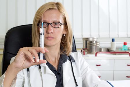 immunize: Female Doctor Preparing Syringe For Vaccination in Clinic