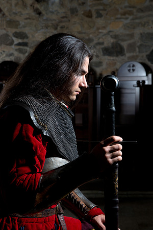 hauberk: Side View of Knight Praying Before the Battle Against Old Stone Wall