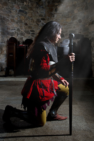 Side View of Knight in Armor With Sword Praying in the Old Church