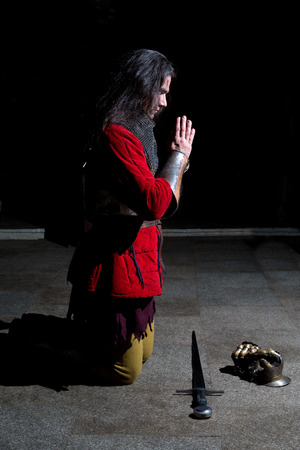 head bowed: Knight Kneeling on His Knees With His Head Bowed and Hands in Prayer in the Old Church Before the Battle