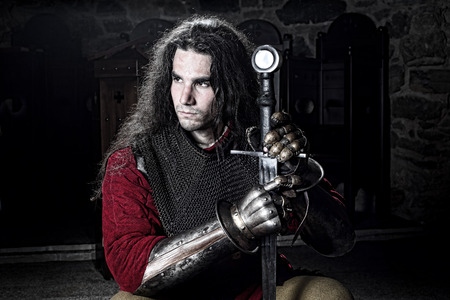 hauberk: Portrait of Serious Knight in Chain Mail With Metal Gloves and Sword Looking Away, Half Length Shot Stock Photo