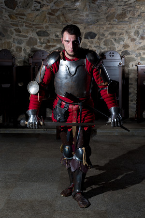 hauberk: Brave Knight in Armor With Sword Standing in Old Church and Looking at Camera Stock Photo