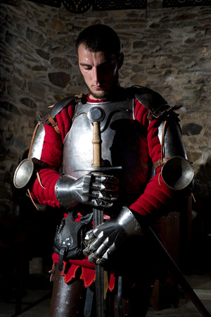 hauberk: Brave Knight Standing With Head Bowed in Prayer and Holding Metal Sword Against Old Stone Wall