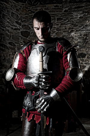 head bowed: Brave Knight Standing With Head Bowed in Prayer and Holding Metal Sword Against Old Stone Wall