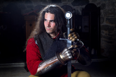 medieval warrior: Portrait of Serious Knight in Chain Mail With Metal Gloves and Sword Looking Away, Half Length Shot Stock Photo