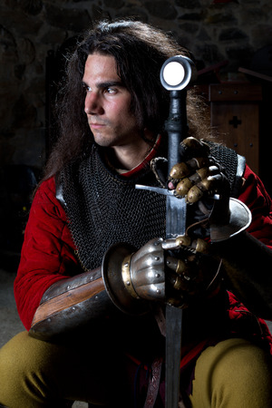 hauberk: Portrait of Knight With Sword Against Black Background Stock Photo