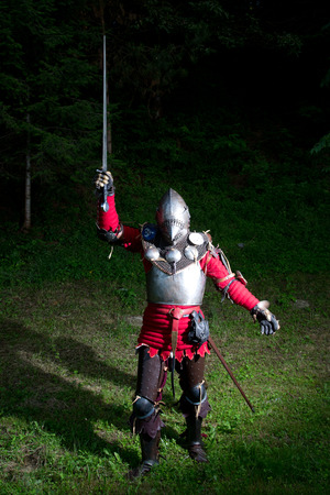 raised hand: Medieval Knight With Sword in Raised Hand in the Forest at Night Stock Photo