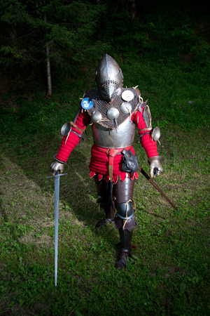 hauberk: Portrait of Knight in Armor With Helmet and Sword in the Forest