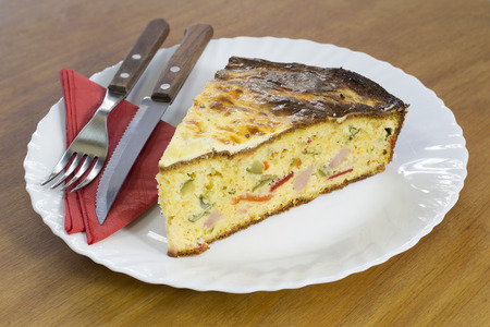 cornbread: Slice of Freshly Baked Cornbread With Vegetables and Ham on White Plate Served to Eat, Wooden Background