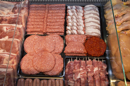 raw: Variety Of Raw Meat - Kebabs Of Minced Meat, Beef Patties, Pork Skewers,Kebabs Wrapped In Bacon, Sausages At The Market Place