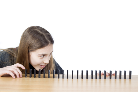 ide: ide View Of Cute Girl Looking At Lined Up Dominoes On Wooden Table Isolated On White Background