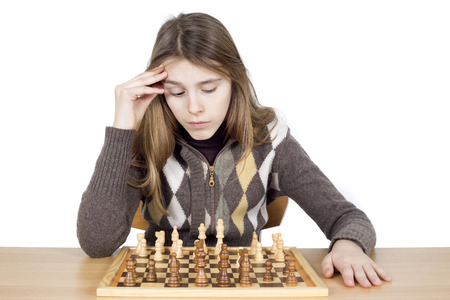 intensely: Studio Shot Of Pensive Young Girl Looking Down At Chessboard And Thinking Intensely About Chess Strategy Isolated On White Background Stock Photo