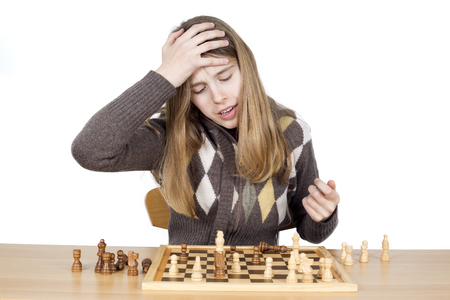 duh: Portrait Of Young Very Disappointed Girl Slapping Hand On Head To Say Duh, Expressing Regret For Mistake She Made During The Chess Game, Studio Shot Isolated On White Stock Photo
