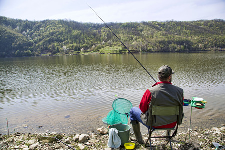 angler: Angler With His Back Towards Camera Sitting On The River Coast Enjoying Angling And Beautiful Nature