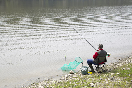 angler: Angler Sitting On The River Coast And Patiently Waiting For Fish To Take A Bait