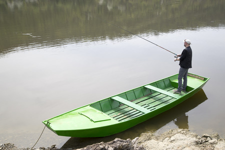 green boat: Sport Fisherman Holding Fishing Rod And Fishing From The Green Boat