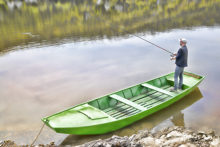 green boat: Sport Fisherman Holding Fishing Rod And Fishing From The Green Boat, Shiny Background Stock Photo