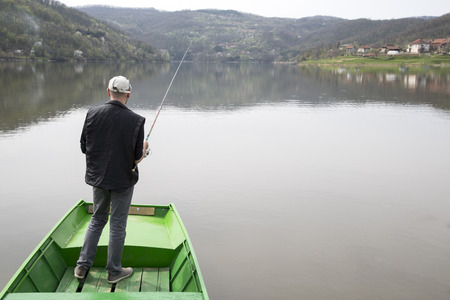 green boat: Man Standing On A Green Boat With His Back Towards The Camera And Fishing On The Calm Lake