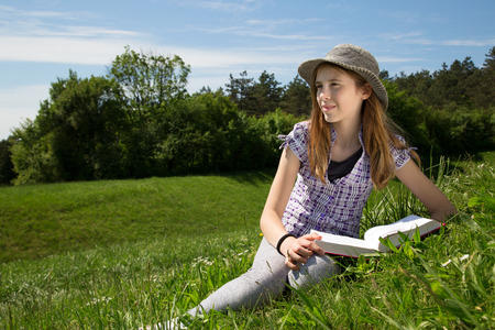 free education: Smiling Young Girl Resting In A Beautiful Field Of Grass Enjoying A Beautiful Sunny Spring Day In Beautiful Nature Stock Photo