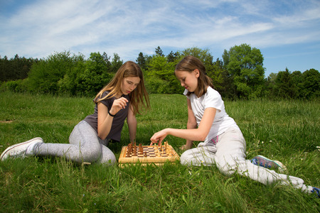 outwit: Two Girls Sitting On The Grass And Playing Chess, Forest Trees And Blue Cloudy Sky In The Background