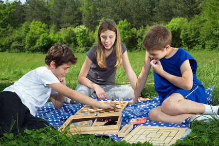 outwit: Group Of Good Friends Sitting On The Grass, Boys Playing Chess And Smiling Girl Enjoying The Game, Forest Trees In The Background Stock Photo