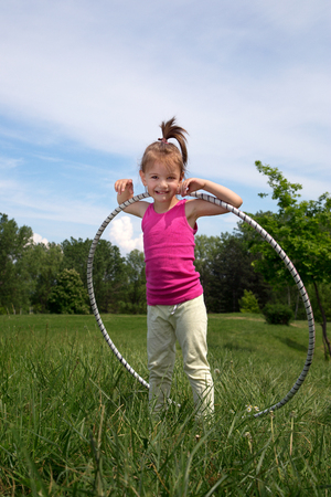 Smiling Little Girl With  Hoop Enjoying Beautiful Spring Day In The Park Stock Photo