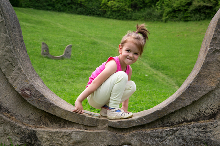 Adorable Smiling Little Girl Crouching On The Stonewall And Looking At The Camera, Green Grass Background Stock Photo