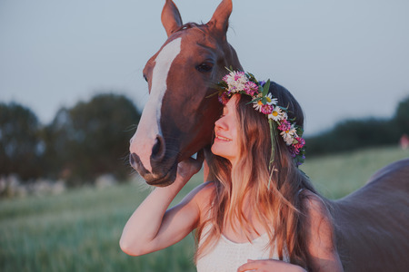 coronet: Smiling girl in floral wreath with horse. Green wheat field.