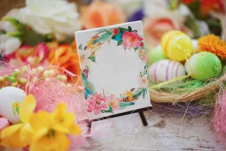seasonal greeting: Joyful colorful spring background for a Happy easter with seasonal greeting handwritten on rustic wooden sign board