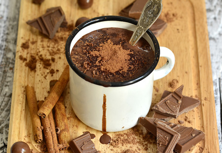 chocolate powder: Hot chocolate in an enamel mug on the wooden board.