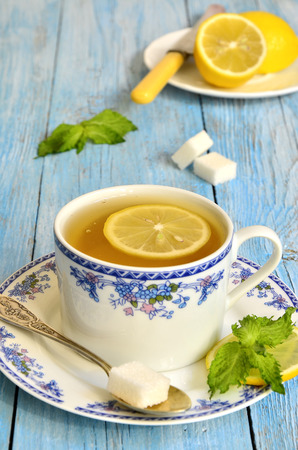 Black tea with lemon and mint on the blue wooden table. photo