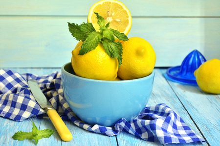Lemons in a blue bowl on the wooden table. photo