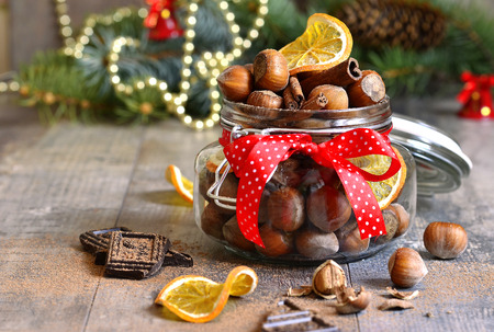 tree nuts: Hazelnuts and christmas spices in a jar on a festive background.
