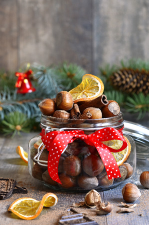 pine nuts: Hazelnuts and christmas spices in a jar on a festive background.