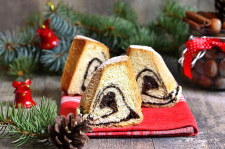 Yeast orange christmas cake with poppy seed filing on a festive background. photo