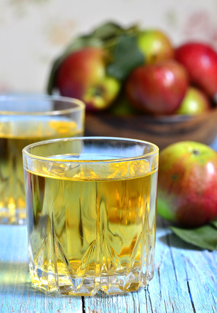 Apple juice in a glass on a blue wooden table. photo
