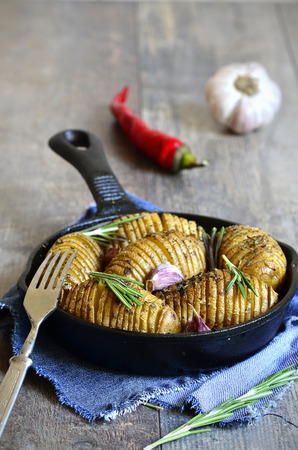 Baked jacket potatoes with garlic and rosemary in a pan. photo