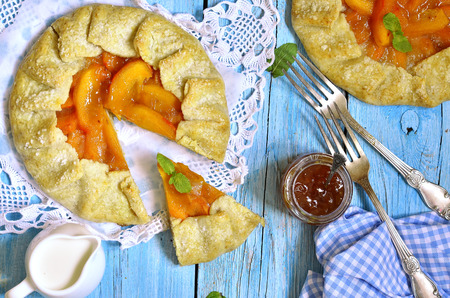 Autumn dessert - persimmon galette on a blue wooden table.