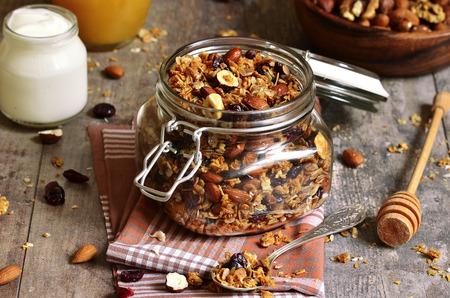 Granola de plusieurs types de céréales avec des noix, des copeaux de noix de coco et de canneberges séchées.