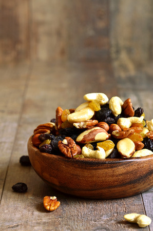 Dried fruits and nuts mix in a wooden bowl. Фото со стока