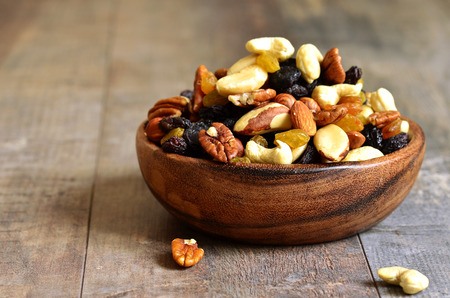 snack: Dried fruits and nuts mix in a wooden bowl. Stock Photo