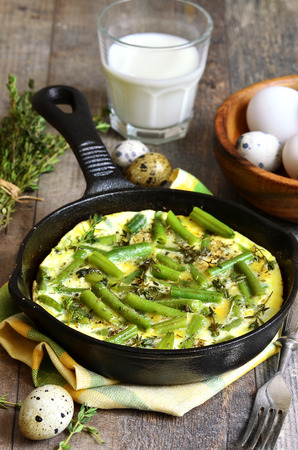 Omelet  with asparagus bean and thyme in a frying pan. photo