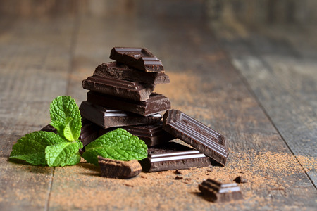 chocolate treats: Stack of chocolate slices with mint leaf on a wooden table. Stock Photo