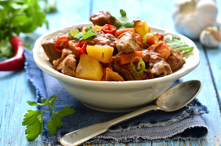Meat stewed with vegetable in spicy tomato sauce on a wooden table. Stockfoto