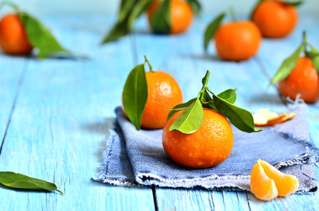 orange peel clove: Tangerines with green leaves in a wooden bowl. Stock Photo